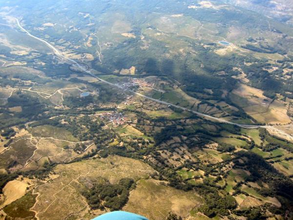 "Well actually 11Km past El Barco and 4 Km before the Tornavacas ""Cherry Tree"" valley of no return. Our eventual field is ringed in the photo. Steve is the white glider low down near the road. I wondered why he was landing where he was, but thought it only polite to join him as it was only the two of us left flying. It all became clear however, as I finished packing up and walked across the road to join him outside of a solitary house which turned out to have a bar in it. Great flight and a cold one waiting for me as I stagger across the road, all courtesy of Steve Ham."